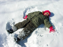 Snow angel. A boy making a snow angel in the snow Stock Photo