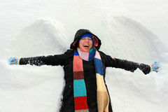Happy young woman having fun, making a snow angel in a deep snow Stock Image