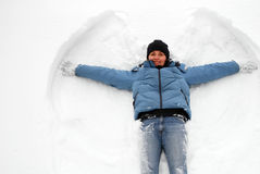 Snow angel. Happy woman on the snow stock photo