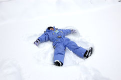 Snow Angel. Young girl in snowsuit making a snow angel stock images