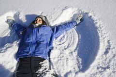 Snow Angel. Young woman making a snow angel Stock Photos