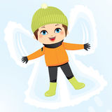Snow Angel Boy. Happy little boy lying down on the ground making a snow angel Stock Image