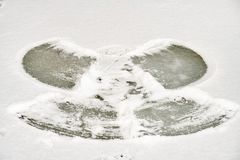 Snow Angel made by a kid in a frozen lake on cold winter morning. royalty free stock photo