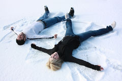 Snow angels. A young couple making snow angels stock photos