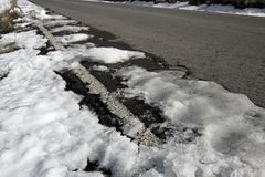 Snow on asphalt road hide white lines Royalty Free Stock Photography