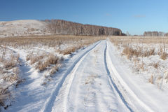 Snow automobile road  going near a hill Bald, Siberia, Russia Royalty Free Stock Photos