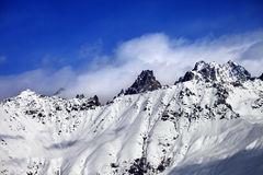 Snow avalanches mountainside in clouds Stock Photo
