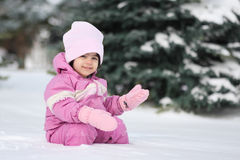 Snow baby. Toddler in the snow in pink snow suite Royalty Free Stock Photo