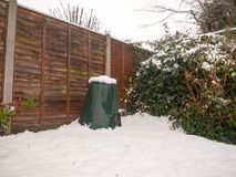 Snow in back garden on green bin lid and fence and floor. Essex; england; uk Stock Photos