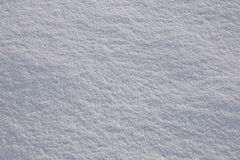 Snow background. Full frame subtle background of fresh white powder snow with texture of shadows and sparkling reflected sunlight Royalty Free Stock Photography