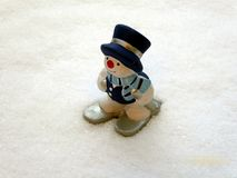 Snow background with a ceramic skiing snowman royalty free stock image