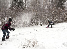Snow ball fight. Children playing outdoors at winter time throwing snow balls at each other Stock Photos
