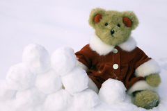 Snow Ball Fight. Teddy bear dressed in a red jump suit and ear muffs  with a mound of snowballs Royalty Free Stock Photo