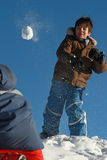 Snow ball fight with his brother. A 10 years old child throws a snowball to his twin brother on a sunny winter day Stock Photo