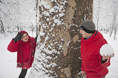 Snow ball fight. Young couple in a snowball fight, hiding over a tree Stock Photo