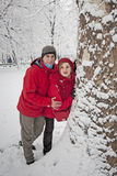 Snow ball fight. Young couple in a snowball fight, hiding over a tree Stock Images