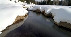 Snow covers and lines a small stream that leads to a forest. Snow banks along a river reflect in the water on a stream stock footage