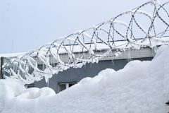 Snow and barbed wire on the fence near the building royalty free stock images