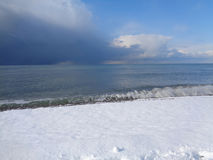 Snow on the beach, Black Sea coast. Snow on the beach and storm clouds over the sea Stock Photography