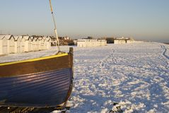 Snow on beach at Worthing. England. Snow on the beach with beach huts and fishing boat at Goring. Worthing. West Sussex. England. Unusual weather - snow not Stock Images