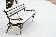 Snow on Bench. Bench in Park covered with Snow on a Cold Winter Day Royalty Free Stock Photos