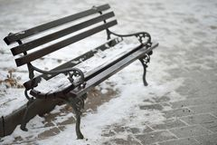 Snow on Bench. Bench on Street covered with Snow on a Cold Winter Day Royalty Free Stock Image