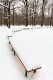 Snow on benches in city park Stock Image