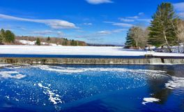 Snow on Big Indian pond with small dam and ice in water. Big Indian pond and little dam with snow cover and ice on water royalty free stock images