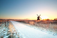 Snow on bike path and sun behind windmill Royalty Free Stock Photos