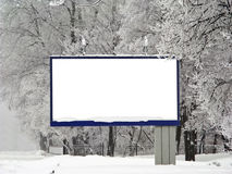 Snow billboard. Billboard covered with snow on the background of the park Stock Image