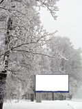 Snow billboard. Billboard covered with snow on the background of the park Royalty Free Stock Images