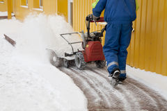 Snow blower. Man working with a snow blowing machine Royalty Free Stock Photo