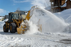 Snow blower. Municipal snow blower clears snow-covered streets producing a plume of snow Royalty Free Stock Photography