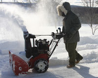 Snow Blower. Man wearing a parka clearing snow from a driveway with a snow blowing machine Royalty Free Stock Photo
