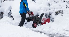 Snow blower clearing driveway after blizzard royalty free stock image
