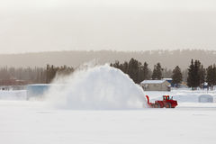 Snow blower clearing road in winter storm blizzard Royalty Free Stock Image