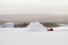 Snow blower clearing road in winter storm blizzard stock images