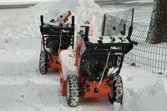 Snow blowers on a break. 2 snow blowers in the snow stock images