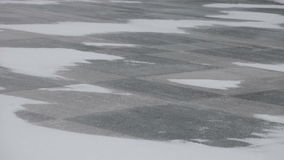Snow blowing and drifting across a stone tiles stock video footage