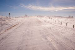 Snow blowing over gravel road in a Saskatchewan winter royalty free stock image