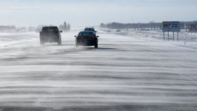 Snow blown highway with traffic. Very windy and brisk day on the highway Stock Photos