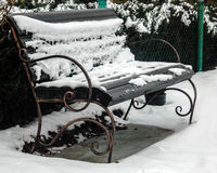 A snow-bound bench is in a garden Stock Photo
