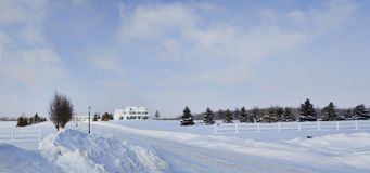 Snow-bound Upscale Home. Upscale rural home surrounded by snow covered fields and fences stock image