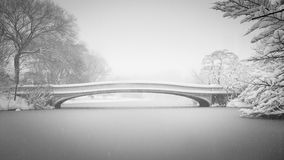 Snow on Bow Bridge and the Lake, Central Park, New. Bow Bridge and the Lake being covered in snow in winter. Black & White photography of Central Parks Bow Royalty Free Stock Images