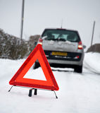 Snow Breakdown. Broken down vehicle in winter snow conditions with red warning triangle Royalty Free Stock Image