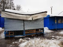 Snow broke the roof of a store or stall in the winter or spring stock photos