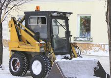 Snow bulldozer - clearing snow on the winter street. Urban landscape Royalty Free Stock Image