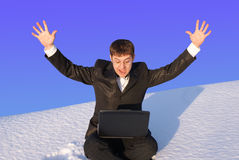 Snow business. The businessman sits in a snow with a computer in a lap Royalty Free Stock Photo