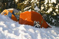 Snow Camping. Two tents at dawn were still lightly dusted with snow after a light storm the evening before stock images