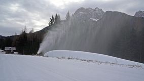 A snow cannon in action. Thruogh the mountains in winter stock video footage